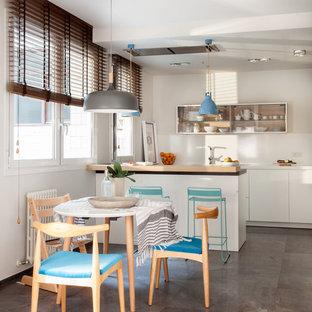 Modelo de cocina comedor de galera, actual, con armarios con paneles lisos, puertas de armario blancas, península, suelo gris, encimeras blancas y salpicadero blanco