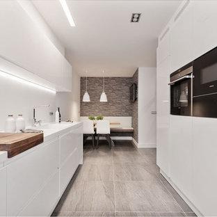 Modelo de cocina comedor lineal, actual, grande, sin isla, con armarios con paneles lisos, puertas de armario blancas, salpicadero blanco, electrodomésticos negros, suelo gris y encimeras blancas