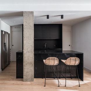 Diseño de cocina comedor en L, contemporánea, con fregadero bajoencimera, armarios con paneles lisos, puertas de armario negras, salpicadero negro, electrodomésticos de acero inoxidable, suelo de madera clara, una isla, suelo beige y encimeras negras
