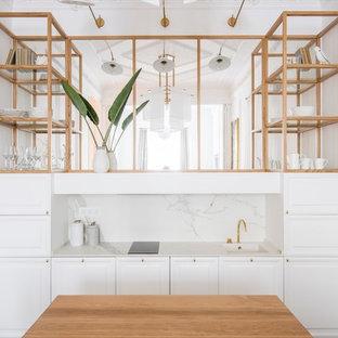 Ejemplo de cocina lineal, contemporánea, de tamaño medio, con puertas de armario blancas, encimera de mármol, salpicadero blanco, salpicadero de mármol, armarios con paneles con relieve y una isla