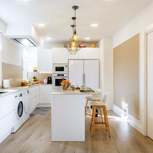 Foto de cocina en L, contemporánea, de tamaño medio, cerrada, con armarios con paneles lisos, puertas de armario blancas, salpicadero beige, electrodomésticos blancos, una isla, suelo de madera clara, suelo beige y encimeras beige