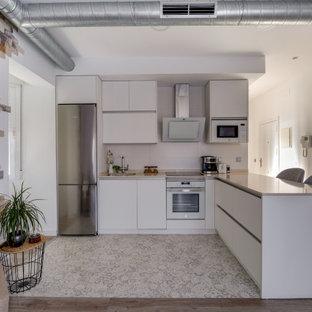 Imagen de cocina en L, contemporánea, con fregadero bajoencimera, armarios con paneles lisos, puertas de armario blancas, electrodomésticos de acero inoxidable, península y suelo blanco