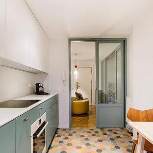 マドリードのエクレクティックスタイルのおしゃれなキッチン (シングルシンク、フラットパネル扉のキャビネット、青いキャビネット、クオーツストーンカウンター、白いキッチンパネル、ライムストーンのキッチンパネル、白い調理設備、セラミックタイルの床、マルチカラーの床、白いキッチンカウンター) の写真
