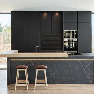 Modelo de cocina moderna con armarios con paneles lisos, puertas de armario negras, electrodomésticos negros, suelo de madera clara, una isla, suelo beige y encimeras grises