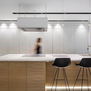 Foto de cocina actual, grande, con fregadero bajoencimera, suelo de cemento, una isla, suelo gris, encimeras blancas y puertas de armario blancas