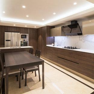 Modelo de cocina comedor contemporánea con armarios con paneles lisos, puertas de armario de madera en tonos medios, electrodomésticos de acero inoxidable, península, encimeras blancas, fregadero bajoencimera, salpicadero blanco y suelo multicolor