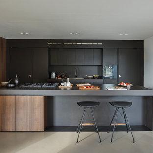 Foto de cocina actual con fregadero bajoencimera, armarios con paneles lisos, puertas de armario negras, salpicadero negro, una isla, suelo gris y encimeras negras