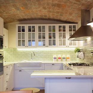 Diseño de cocina en U, clásica renovada, con puertas de armario blancas, electrodomésticos de acero inoxidable, península, fregadero sobremueble, armarios tipo vitrina y salpicadero de azulejos tipo metro