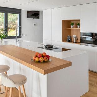 Diseño de cocina costera con armarios con paneles lisos, puertas de armario blancas, una isla, encimeras blancas, fregadero de un seno y suelo de madera clara