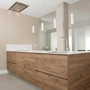 Foto de cocina lineal, actual, con armarios con paneles lisos, puertas de armario de madera oscura, península, suelo gris y encimeras blancas