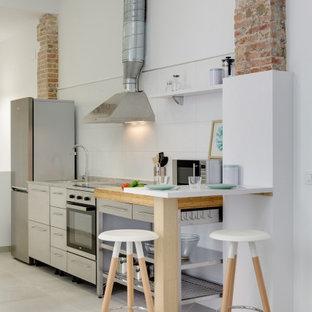 Foto de cocina lineal, actual, con armarios con paneles lisos, puertas de armario grises, electrodomésticos de acero inoxidable, suelo gris y encimeras grises