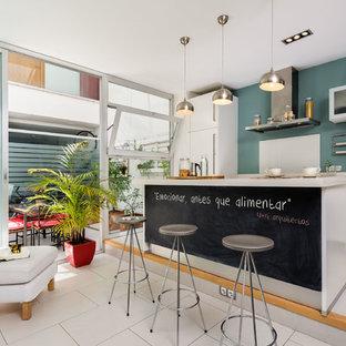 Modelo de cocina lineal, contemporánea, de tamaño medio, abierta, con armarios con paneles lisos, puertas de armario blancas, salpicadero azul, una isla y suelo blanco