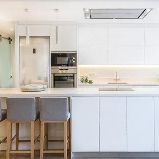 Foto de cocina comedor en L, minimalista, de tamaño medio, con fregadero bajoencimera, armarios con paneles lisos, puertas de armario blancas, salpicadero blanco, electrodomésticos de acero inoxidable y una isla