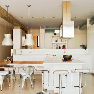 Ejemplo de cocina lineal, industrial, grande, abierta, con armarios con paneles lisos, puertas de armario blancas, suelo de cemento, una isla, salpicadero blanco y electrodomésticos de acero inoxidable