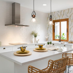 Design ideas for a contemporary l-shaped kitchen in Other with a drop-in sink, shaker cabinets, white cabinets, white splashback, terra-cotta splashback, with island, multi-coloured floor and white benchtop.