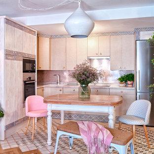 Imagen de cocina en L, costera, abierta, sin isla, con fregadero encastrado, armarios con paneles lisos, puertas de armario beige, electrodomésticos de acero inoxidable, suelo multicolor y encimeras grises