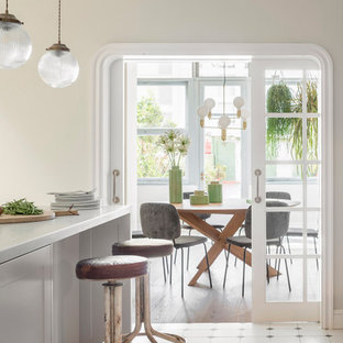 Design ideas for a large shabby-chic style single-wall open plan kitchen in Barcelona with a double-bowl sink, white cabinets, marble benchtops, stainless steel appliances, medium hardwood floors, a peninsula, multi-coloured floor and white benchtop.