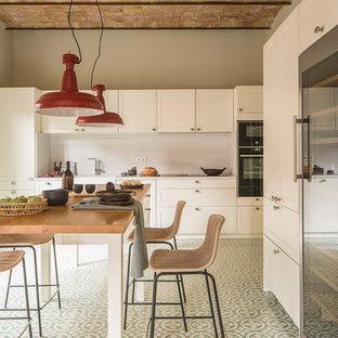 Einzeilige, Mittelgroße Mediterrane Wohnküche mit integriertem Waschbecken, weißen Schränken, Arbeitsplatte aus Holz, Küchenrückwand in Weiß, Kalk-Rückwand, Kücheninsel, brauner Arbeitsplatte, Schrankfronten im Shaker-Stil, schwarzen Elektrogeräten und grünem Boden in Barcelona