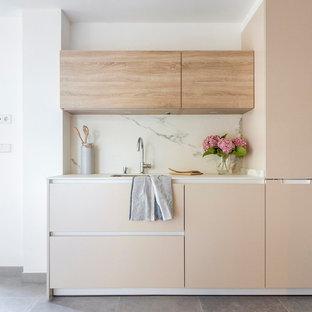 Modelo de cocina lineal, actual, pequeña, con armarios con paneles lisos, puertas de armario beige, salpicadero blanco, salpicadero de mármol, suelo gris y fregadero bajoencimera