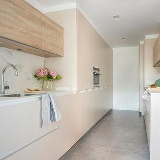 Diseño de cocina de galera, actual, de tamaño medio, con armarios con paneles lisos, puertas de armario beige, salpicadero blanco, salpicadero de mármol y suelo gris