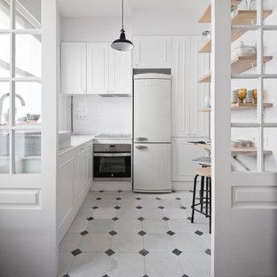 Imagen de cocina en L, nórdica, cerrada, sin isla, con armarios con paneles empotrados, puertas de armario blancas, salpicadero blanco, salpicadero de azulejos tipo metro, electrodomésticos blancos, suelo blanco y encimeras blancas