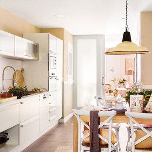 Foto de cocina comedor lineal, romántica, grande, sin isla, con armarios estilo shaker, puertas de armario blancas, electrodomésticos de acero inoxidable, suelo de baldosas de cerámica y suelo marrón