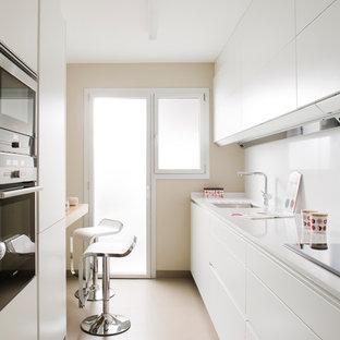 Modelo de cocina de galera, moderna, de tamaño medio, con electrodomésticos de acero inoxidable, salpicadero blanco, fregadero bajoencimera, armarios con paneles lisos, puertas de armario blancas, península, suelo beige y encimeras blancas