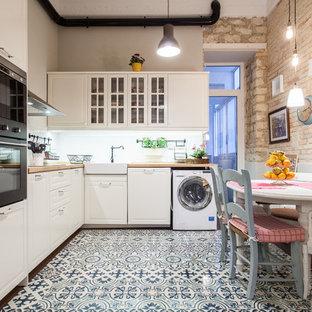 Exempel på ett mellanstort klassiskt kök, med en rustik diskho, vita skåp, träbänkskiva, vitt stänkskydd, svarta vitvaror, klinkergolv i keramik, luckor med glaspanel och flerfärgat golv