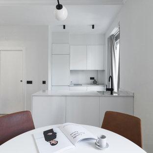 Ejemplo de cocina comedor de galera, contemporánea, pequeña, con fregadero bajoencimera, armarios con paneles lisos, puertas de armario blancas, electrodomésticos con paneles, suelo de madera clara, península, suelo beige y encimeras blancas