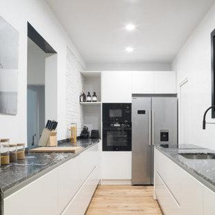 Ejemplo de cocina en U, actual, sin isla, con fregadero bajoencimera, armarios con paneles lisos, puertas de armario blancas, electrodomésticos de acero inoxidable, suelo de madera clara, suelo beige y encimeras negras