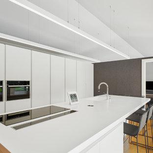 Diseño de cocina minimalista con fregadero de un seno, armarios con paneles lisos, puertas de armario blancas, electrodomésticos negros, suelo de madera en tonos medios, una isla y encimeras blancas