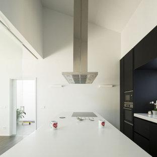 Diseño de cocina de galera, moderna, con fregadero integrado, armarios con paneles lisos, puertas de armario negras, salpicadero blanco, electrodomésticos negros y una isla