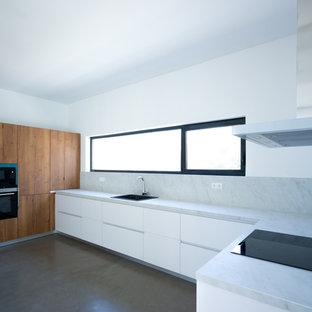 マラガの大きいコンテンポラリースタイルのおしゃれなキッチン (アンダーカウンターシンク、フラットパネル扉のキャビネット、中間色木目調キャビネット、クオーツストーンカウンター、白いキッチンパネル、大理石のキッチンパネル、パネルと同色の調理設備、コンクリートの床、アイランドなし、グレーの床) の写真