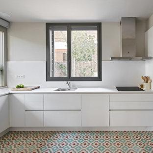 Modelo de cocina en L, actual, con fregadero bajoencimera, armarios con paneles lisos, puertas de armario blancas, electrodomésticos de acero inoxidable, suelo multicolor y encimeras blancas