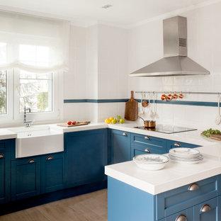Ejemplo de cocina en U, marinera, de tamaño medio, con puertas de armario azules, salpicadero blanco, salpicadero de azulejos de cerámica, península, fregadero sobremueble, armarios estilo shaker y suelo beige