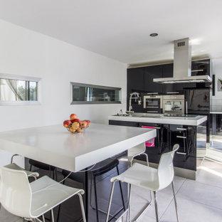 Ejemplo de cocina comedor de galera, actual, de tamaño medio, con armarios con paneles lisos, puertas de armario negras, electrodomésticos con paneles, una isla, suelo gris y encimeras blancas