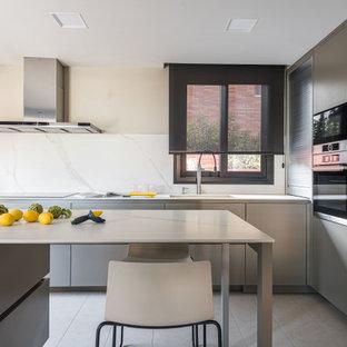 Ejemplo de cocina en L, contemporánea, con fregadero bajoencimera, armarios con paneles lisos, puertas de armario grises, salpicadero blanco, salpicadero de losas de piedra, electrodomésticos de acero inoxidable, una isla, suelo gris y encimeras blancas