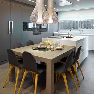 Cette photo montre une cuisine tendance avec un sol en carrelage de céramique, un placard à porte plane, des portes de placard marrons et un électroménager noir.