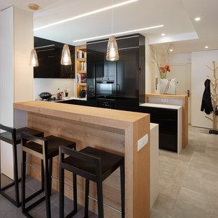 Ejemplo de cocina en U, contemporánea, de tamaño medio, abierta, con armarios con paneles lisos, puertas de armario negras, electrodomésticos negros, suelo de baldosas de cerámica y península