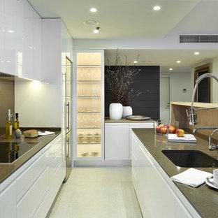 Diseño de cocina de galera, actual, de tamaño medio, abierta, con fregadero bajoencimera, armarios con paneles lisos, salpicadero marrón, electrodomésticos de acero inoxidable, una isla y puertas de armario blancas
