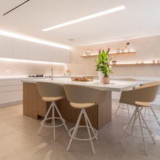 Ejemplo de cocina en L, contemporánea, grande, con fregadero bajoencimera, armarios con paneles lisos, puertas de armario blancas, salpicadero beige, electrodomésticos con paneles, suelo de baldosas de porcelana, una isla, suelo negro y encimeras blancas