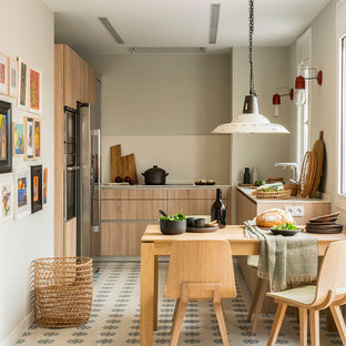 Photo of a mid-sized beach style u-shaped eat-in kitchen in Barcelona with an integrated sink, flat-panel cabinets, light wood cabinets, laminate benchtops, beige splashback, stainless steel appliances, beige benchtop, no island and multi-coloured floor.