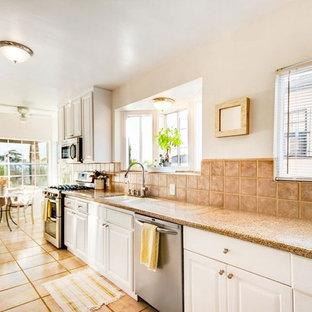 ロサンゼルスの中サイズのエクレクティックスタイルのおしゃれなキッチン (ダブルシンク、インセット扉のキャビネット、白いキャビネット、御影石カウンター、ベージュキッチンパネル、セラミックタイルのキッチンパネル、シルバーの調理設備の、セラミックタイルの床、アイランドなし、ベージュの床、マルチカラーのキッチンカウンター) の写真