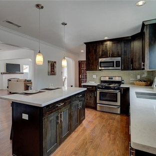 Photo of a large classic u-shaped open plan kitchen in Los Angeles with a double-bowl sink, beaded cabinets, distressed cabinets, granite worktops, green splashback, porcelain splashback, stainless steel appliances, plywood flooring, an island, brown floors and white worktops.