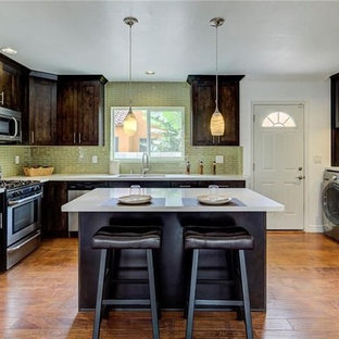 Design ideas for a large classic u-shaped open plan kitchen in Los Angeles with a double-bowl sink, beaded cabinets, distressed cabinets, granite worktops, green splashback, porcelain splashback, stainless steel appliances, plywood flooring, an island, brown floors and white worktops.