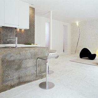 Modelo de cocina lineal, actual, de tamaño medio, abierta, con armarios con paneles lisos, puertas de armario blancas, salpicadero verde y una isla