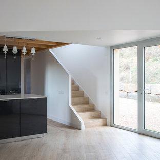 Diseño de comedor moderno, grande, abierto, con paredes blancas, suelo de madera en tonos medios, chimenea de esquina y marco de chimenea de yeso