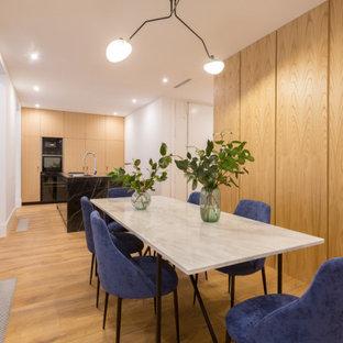 Foto de comedor actual con paredes blancas, suelo de madera en tonos medios y suelo marrón