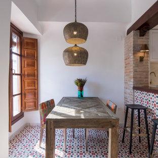 Foto di una sala da pranzo aperta verso la cucina mediterranea di medie dimensioni con pareti bianche, pavimento multicolore e pavimento con piastrelle in ceramica