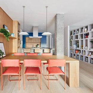 Ejemplo de comedor actual, abierto, con paredes marrones, suelo de madera clara y suelo beige